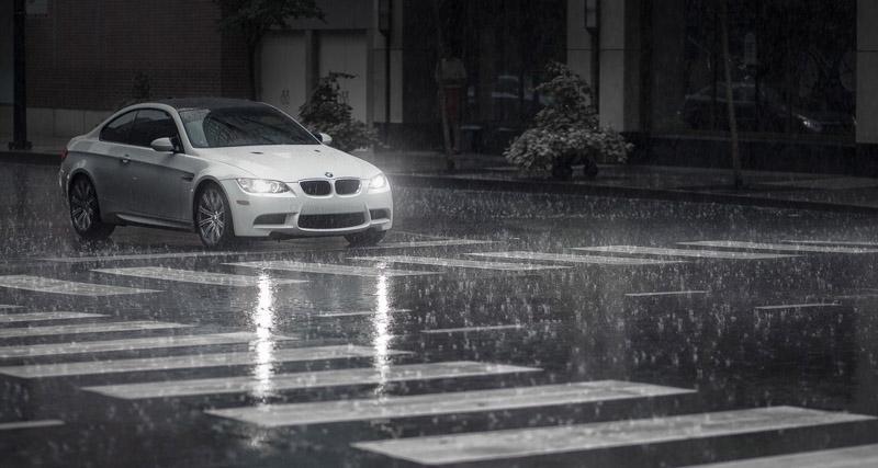 Un coche color blanco esta recorriendo baja la lluvia fuerrte