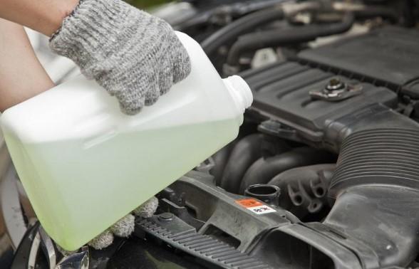 un hombre cambia el líquido refrigerante para autos