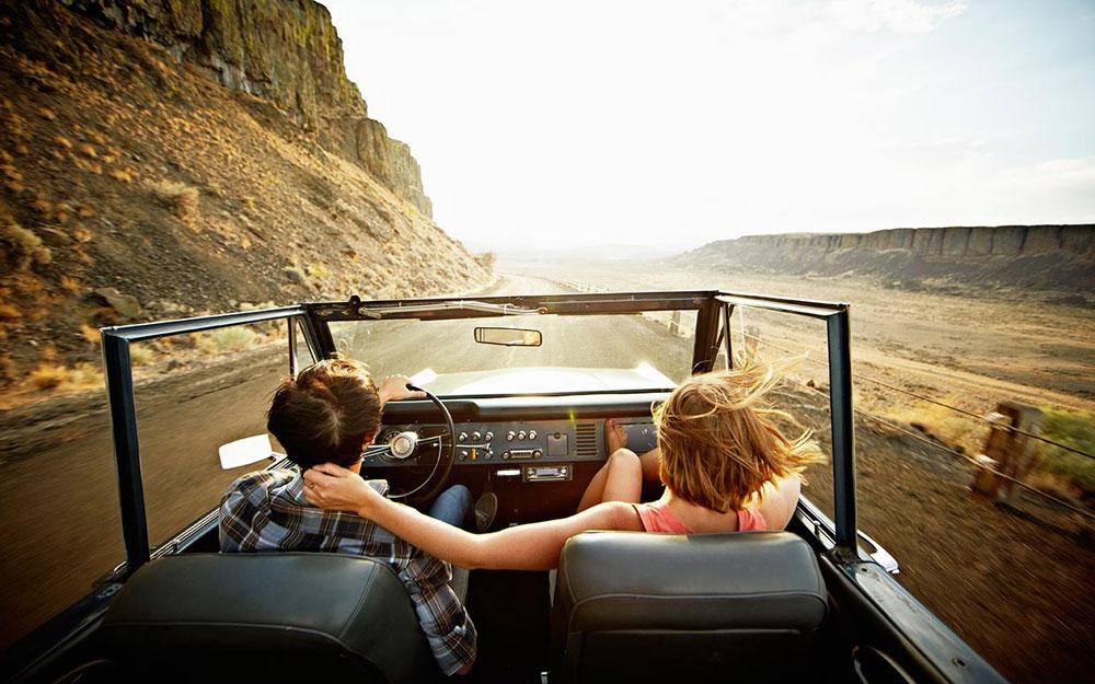 dos personas viajan en auto