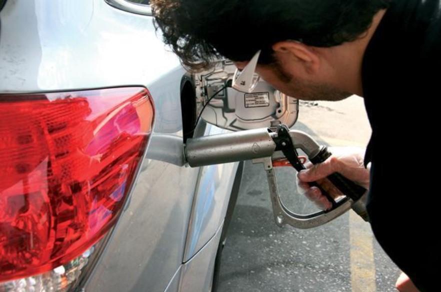 un hombre esta sacando combustible de un auto