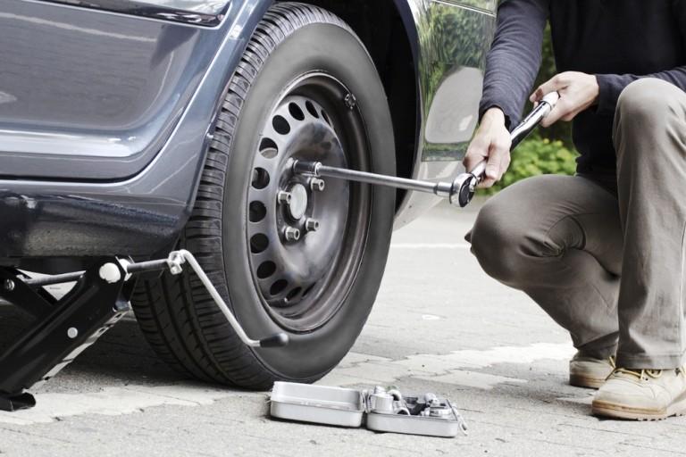 un hombre esta cambiando ruedas de repuesto para autos