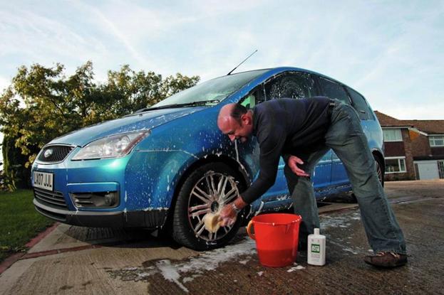 Un hombre está limpia un auto de color azul