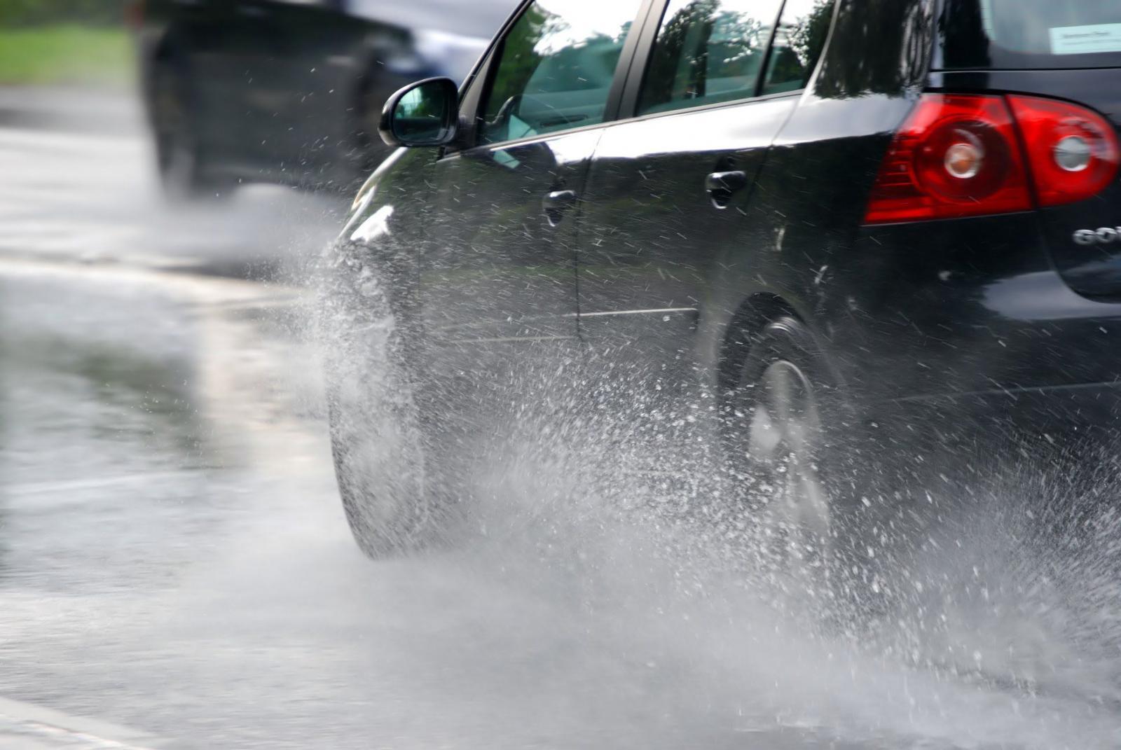 Un auto corriendo bajo la lluvia