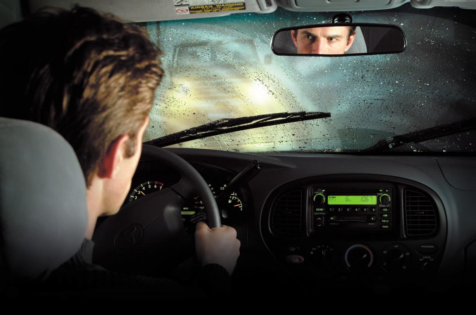 Un hombre en un auto está a conducir bajo la lluvia