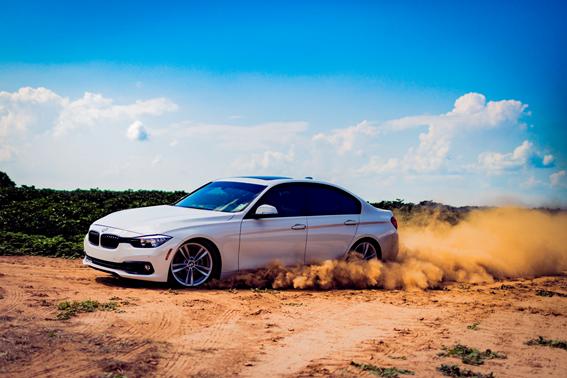 Coche BMW de color blanco en la tierra batida