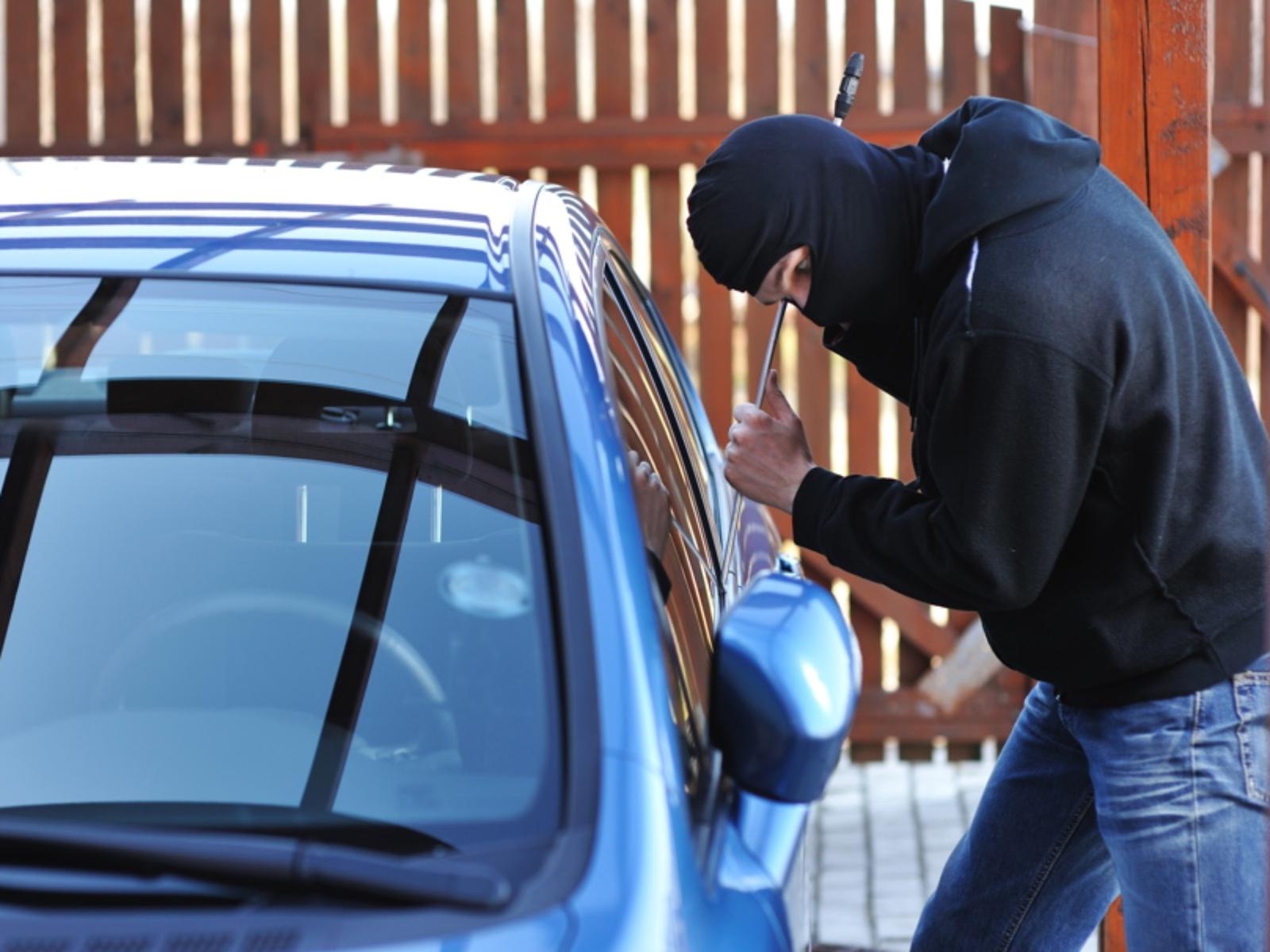 Un hombre está intentando abrir la puerta de un auto