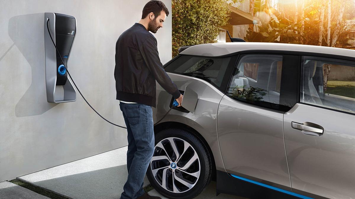 Hombre carga su auto eléctrico