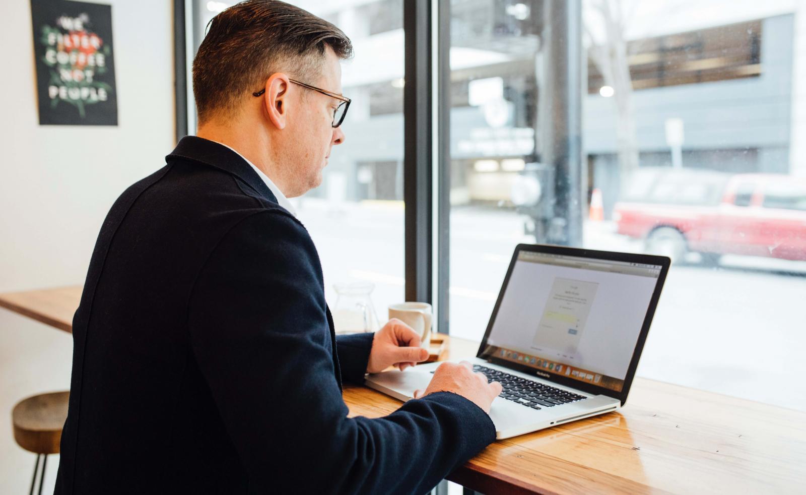 Arrendar un auto: Un hombre está trabajando con su portátil